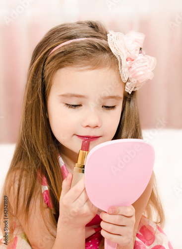 Little girl with lipstick and  mirror