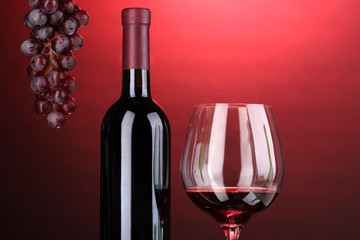 Bottle of great wine and wineglass on red background