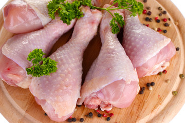 Raw Chicken Drumsticks with parsley and pepper on cutting board