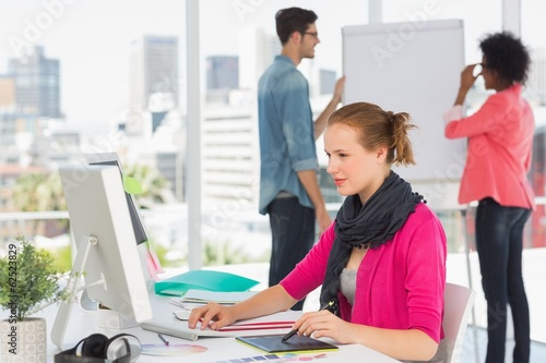 Female artist using graphic tablet with colleagues at office