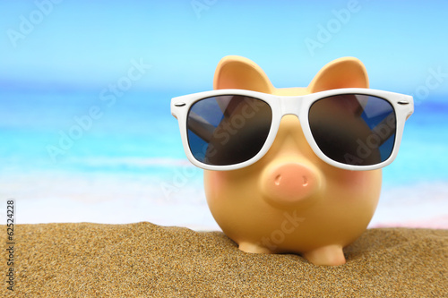 Foto op Canvas Strand Summer piggy bank with sunglasses on the beach