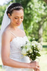 Shy bride holding flower bouquet in garden