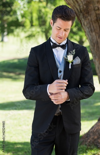 Handsome groom adjusting sleeve in garden