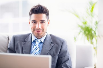 Handsome businessman sitting on sofa using his laptop