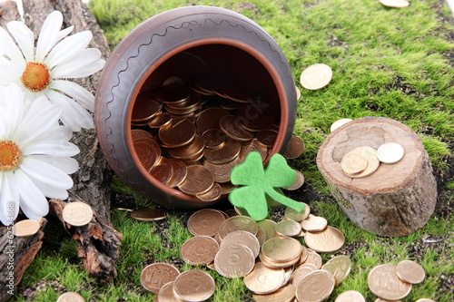 Golden coins falling out from pot, on bright background