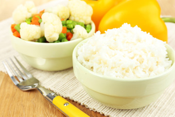 Cooked rice with vegetables on wooden table close up