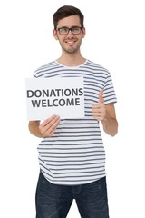 Man holding a donation welcome note while gesturing thumbs up