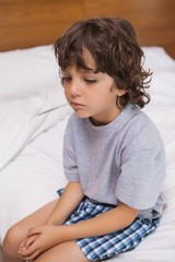 Sick child with thermometer sitting in bed