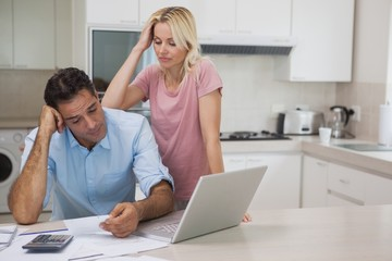 Unhappy couple with bills and laptop in kitchen