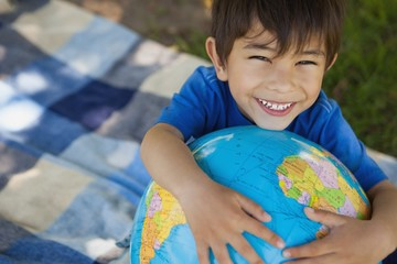 Close-up portrait of a cute boy holding globe