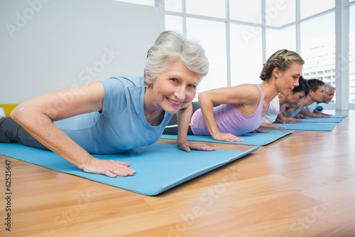 Papiers peints Fitness Group doing cobra pose in row at yoga class