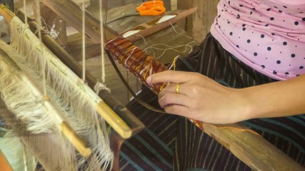 Woman working on a loom. Laos