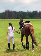 Groom girl with race horse walking away