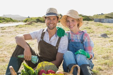 Couple with fresh vegetables in field