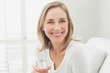 Portrait of a smiling relaxed woman with a glass of water
