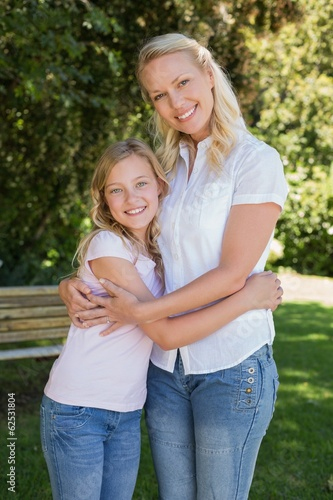 Mother and daughter embracing in park