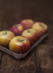 Äpfel in Verpackung auf Holz
