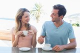Happy young couple having coffee at table