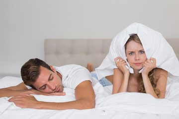 Angry woman holding pillow besides a sleeping man in bed