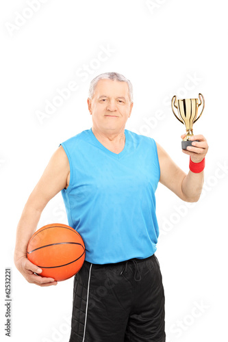 Mature athlete holding basketball and a trophy