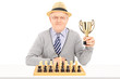 Senior chess player holding a trophy