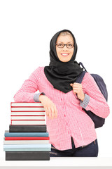 Religious female student leaning on a stack of books