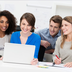 gruppe junger leute schaut auf laptop