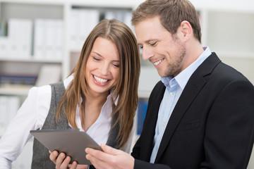 zwei lächelnde kollegen schauen auf tablet-pc
