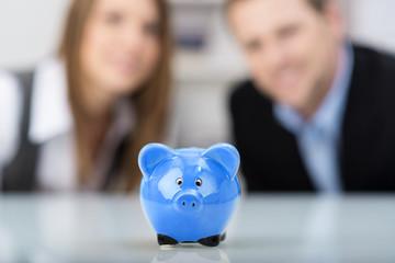 zwei personen schauen auf blaues sparschwein