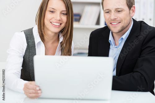 lächelndes paar schaut auf laptop