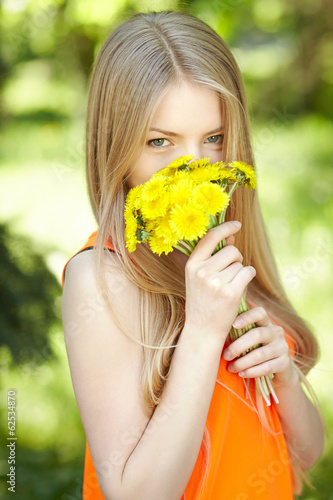 Girl smelling bunch of dandelions