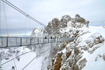 People crossing a bridge between mountains