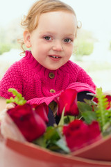 Beautiful little girl with a large bouquet of flowers