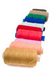 Pile of coloured bobbins of thread