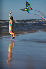 Young woman playing with kite on the beach