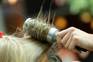 Hairdresser combing hair by hairbrush and hair dryer
