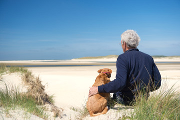 Man with dog on sand dune