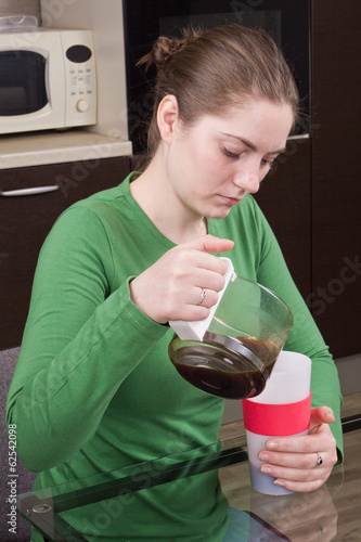 Sleepy girl pouring coffee in cup