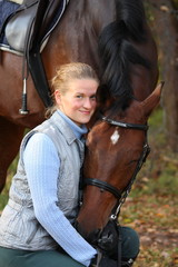 Beautiful blonde woman and brown horse