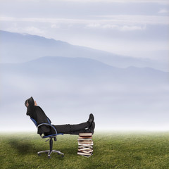 Businessman in office chair in field with mountains