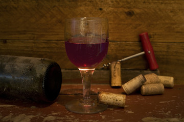 glass of wine with corks and corkscrew, selective focus