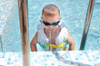 Little boy spitting out a mouthful of water