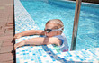 Small boy clambering out swimming pool