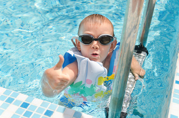 Young boy in a swimming pool giving a thumbs up