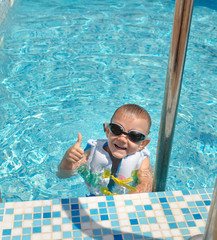 Happy goung boy in a swimming pool giving a thumbs up