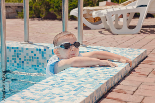 Small boy clambering out of a swimming pool