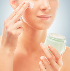Woman applies cream on face, close-up