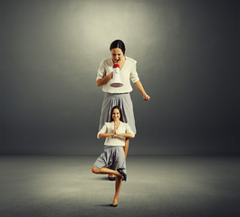 woman screaming at small yoga woman over dark