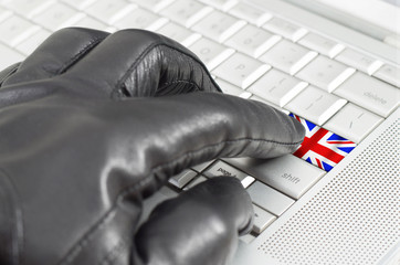 Hacking UK concept with hand wearing black leather glove pressin