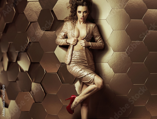 Sexy woman leaning against wall of plates